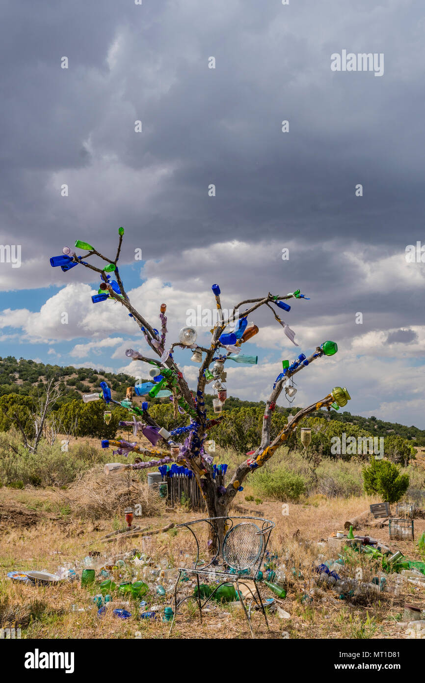 A tree that has glass bottles attached to its branches as a work of primitive or folk art in Golden, New Mexico. - Stock Image