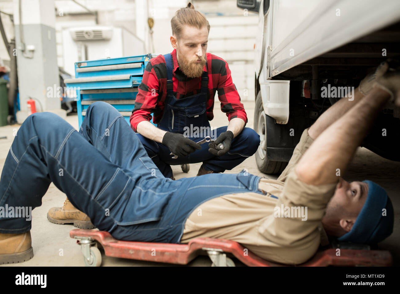 Mechanics Repairing Vehicle In Garage - Stock Image
