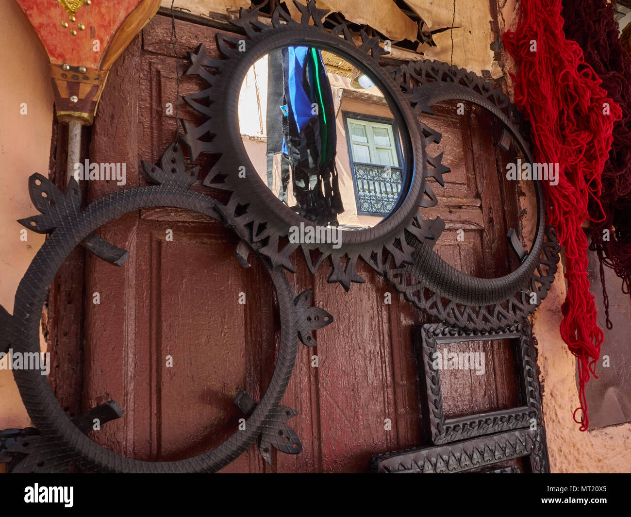 Round Mirror In A Metal Frame On The Burgundy Wall Next To Two Empty Round Metal Frames Stock Photo Alamy