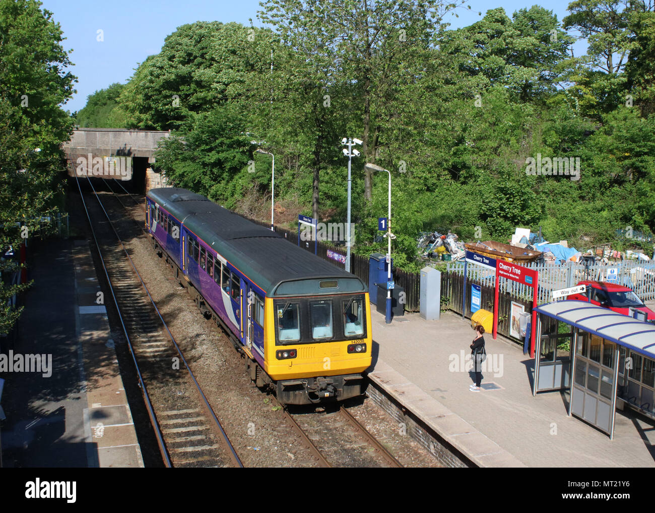 Class 142 Pacer two car dmu train in Northern livery arriving at Cherry Tree railway station, Lancashire, with a passenger waiting on the platform. - Stock Image