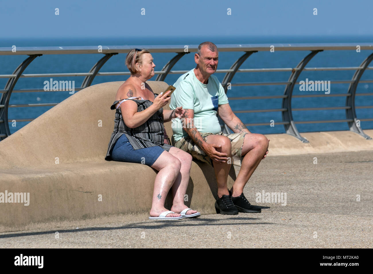 Woman shading herself from the sun in Blackpool, Lancashire. UK Weather.  28th May, 2018.  Bright sunny start to the day at the coast as holidaymakers and tourists enjoy the amenities and attractions on the seafront promenade. in warm sunshine. Credit:MediaWorldImages/AlamyLiveNews - Stock Image