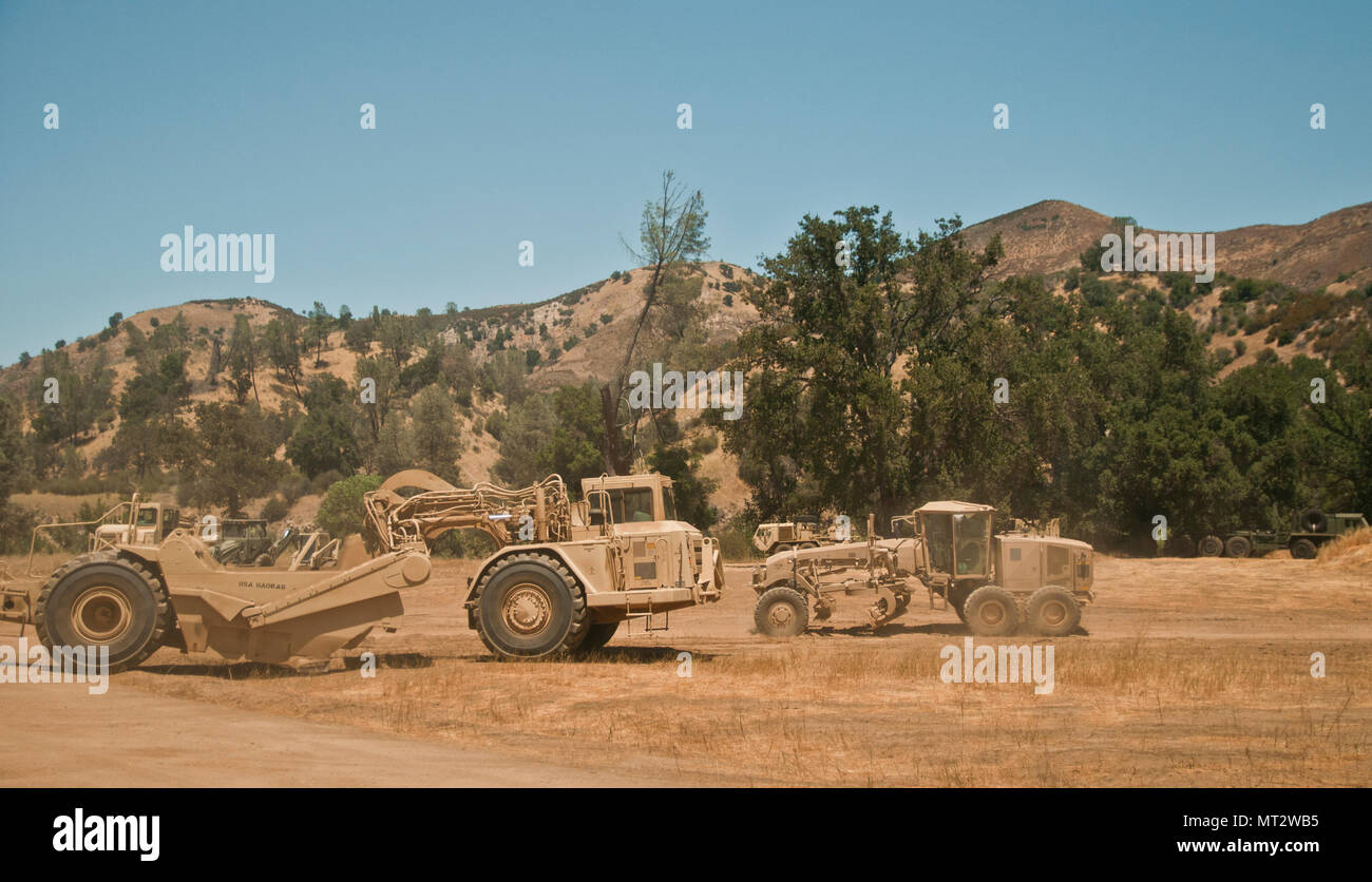 Engineers drive a grader and a scraper by each other while