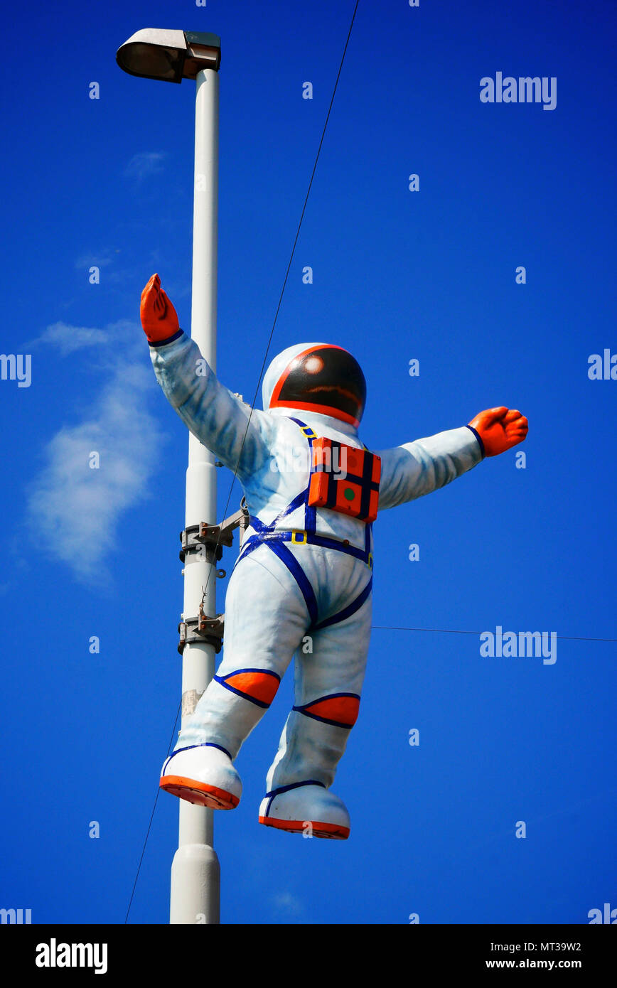 Astronaut in space suit attached to lamp post set against blue sky - Stock Image