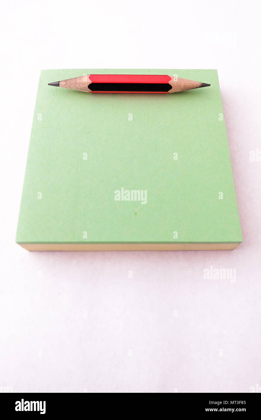 Small red and black pencil, sharpened at both ends, on a green notepad - Stock Image