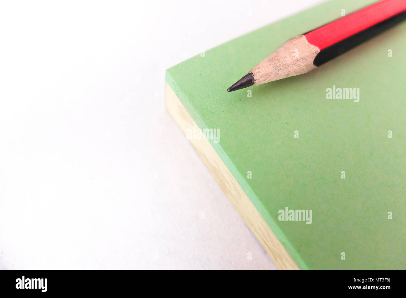 Small red and black pencil, sharp at both ends, on a green and yellow notepad - Stock Image