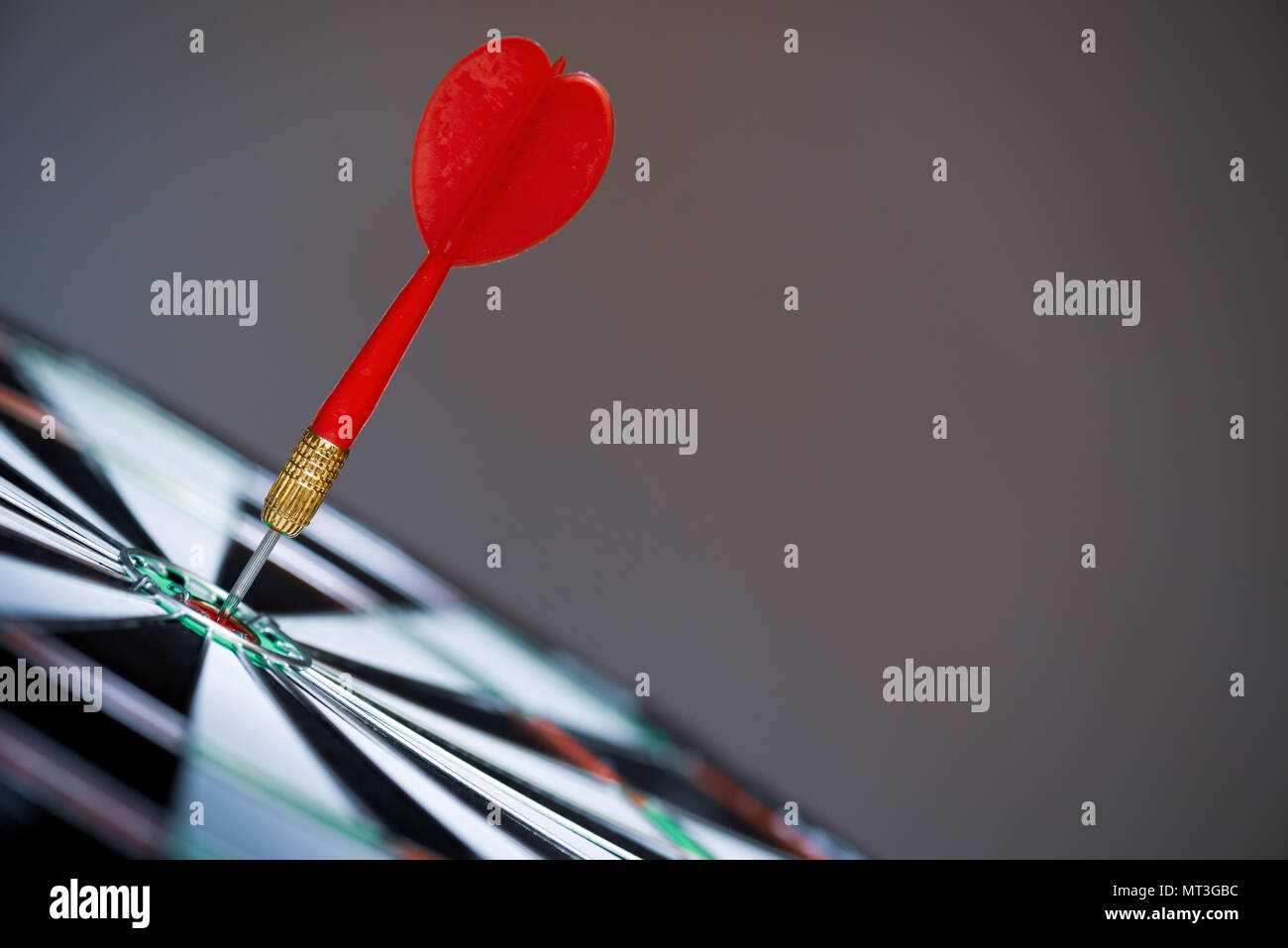 Close up shot red darts arrows in the target center on dark background. Business target or goal success and winner concept. - Stock Image