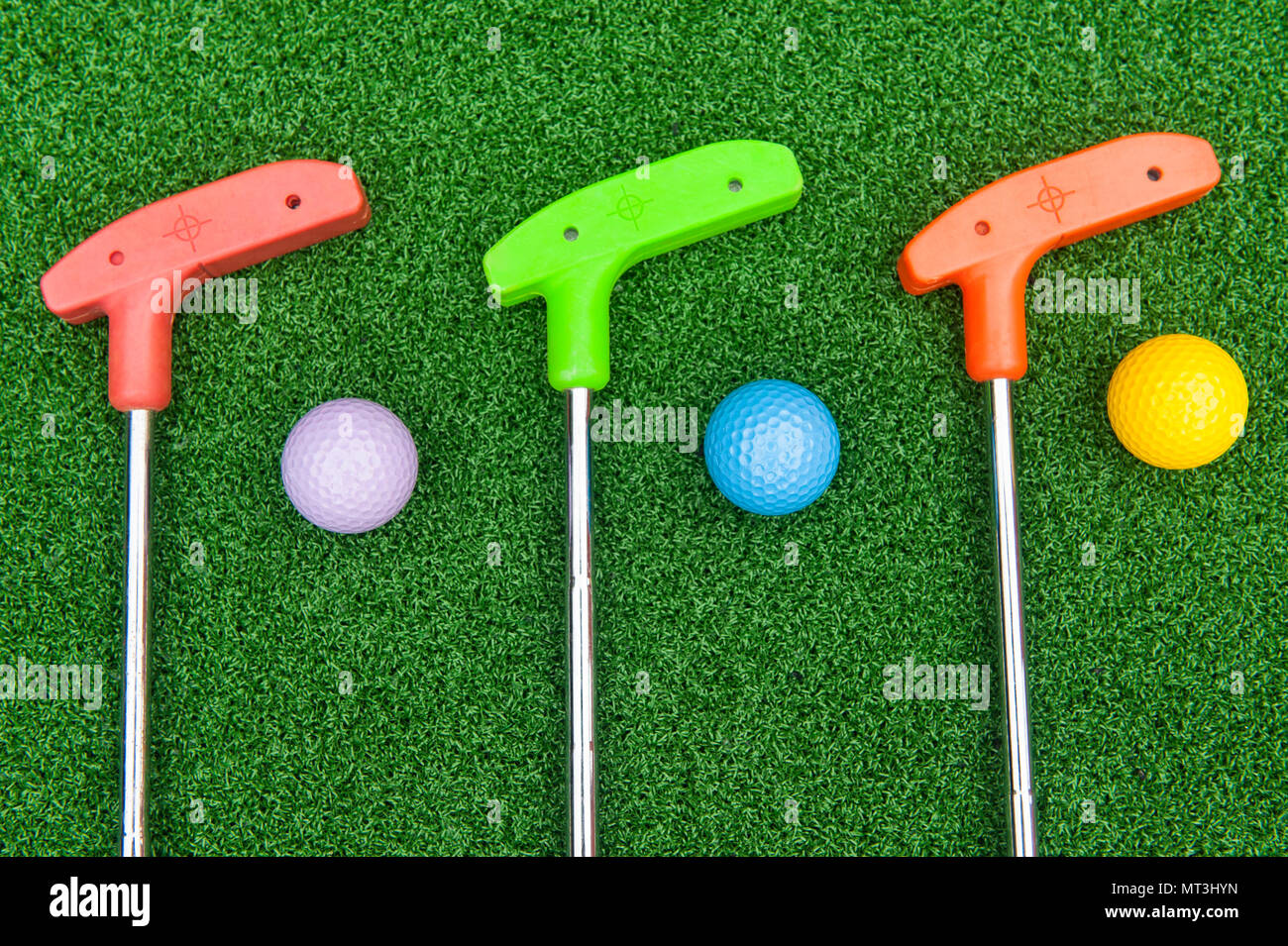 Three colorful rubber golf clubs with balls for miniature golf Stock Photo