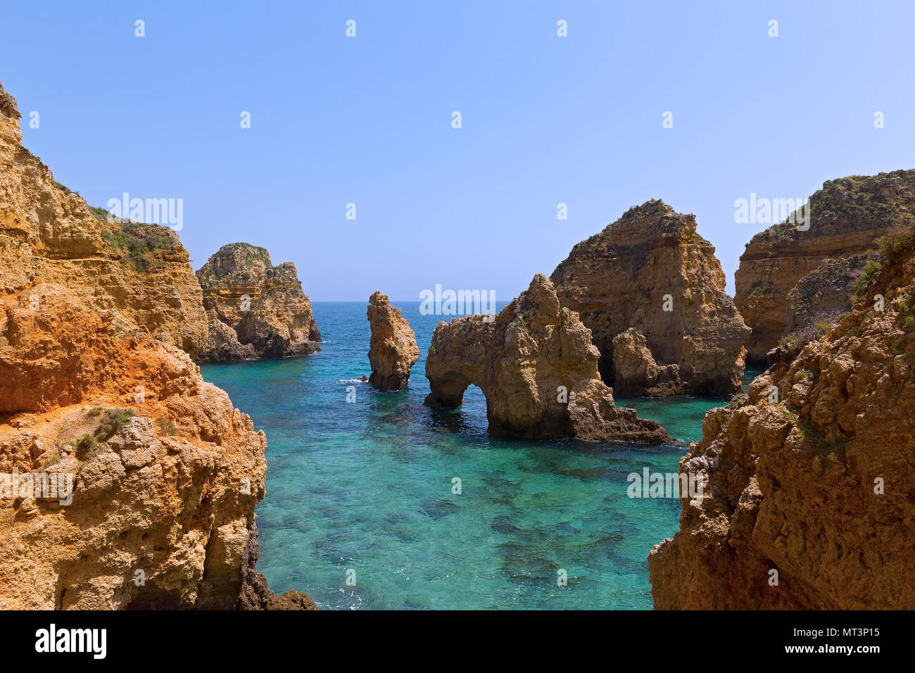 Rocky cliffs and grottoes in Algarve, Portugal. Cliffs and turquoise sea waters on a warm spring morning. Stock Photo