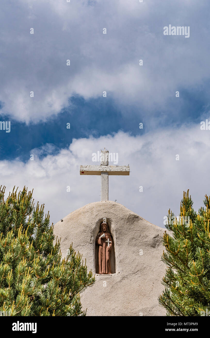 Detail of the cross and the niche holding a religious figure at the San Francisco de Asis Catholic Church in Golden, New Mexico. It was established in - Stock Image