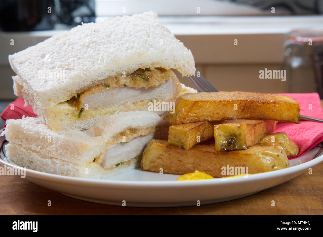 A snack/lunch of fried breaded Pork steak sandwich with white sliced bread and potato chips/fries - Stock Image