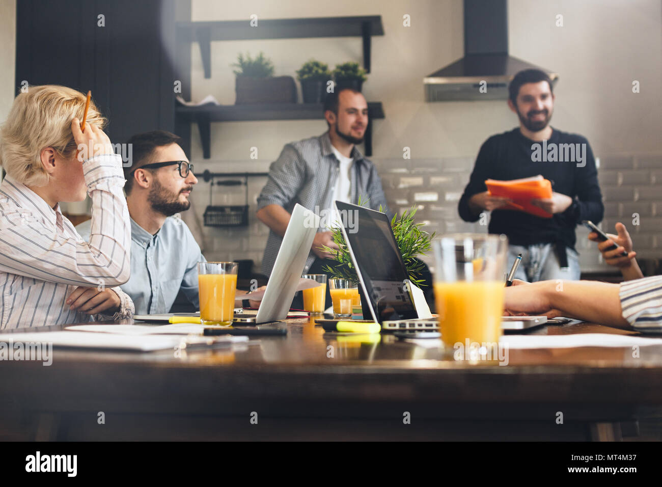 Group of creative coworkers brainstorming at kitchen. Business people working together and using laptops. Young team of managers making great business Stock Photo