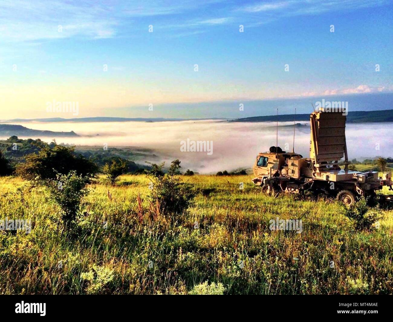 The radar section of 3rd Battalion, 29th Field Artillery Regiment, 3rd Armored Brigade Combat Team, 4th Infantry Division, sets up for a combined arms live-fire exercise in the morning mist of a valley at the Cincu Joint National Training Center, Romania, July 14, 2017. The radar detects and identifies enemy mortars, cannons and rockets, and it is an asset critical to helping the 'Iron Brigade' win a 'deep fight' prior to front-line encounters with an enemy. (U.S. Army photo by 3rd Armored Brigade Combat Team, 4th Infantry Division) - Stock Image