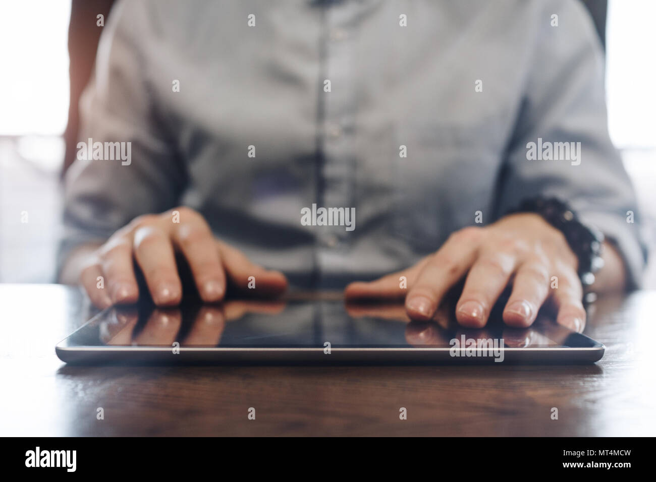 Account manager working and typing on modern tablet. Tablet close up on wooden desk in a modern open office. Men's hands touching screen tablet - Stock Image