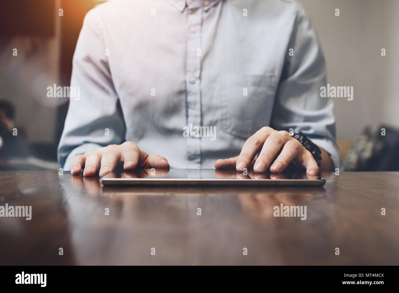 Closeup photo of male hands touching screen tablet. Modern tablet on large wooden table. Businessman typing text on tablet - Stock Image