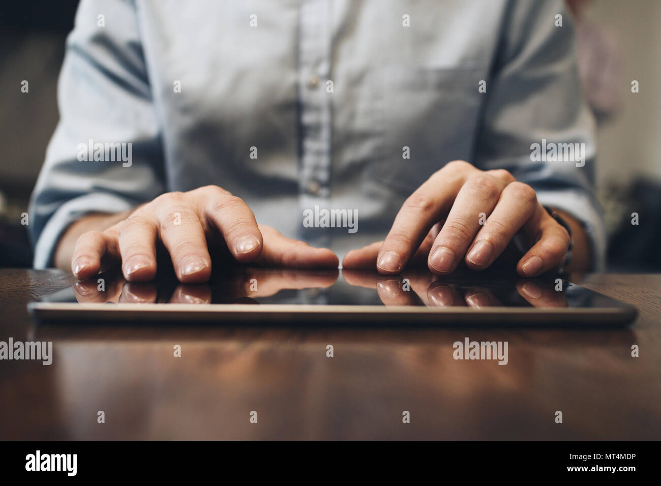Close up view on male hands typing on screen modern tablet. Computer touch pad on wooden table - Stock Image