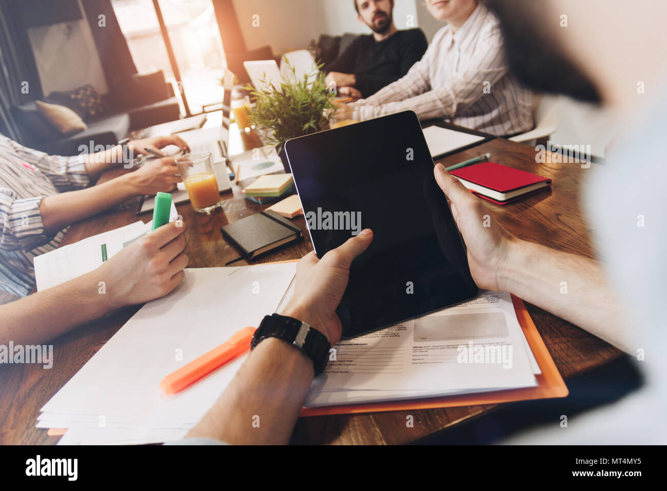 Man holds touch tablet in his hand and discusses with coworkers a new business plan. POV view of male hands holds modern tablet on background of woode Stock Photo