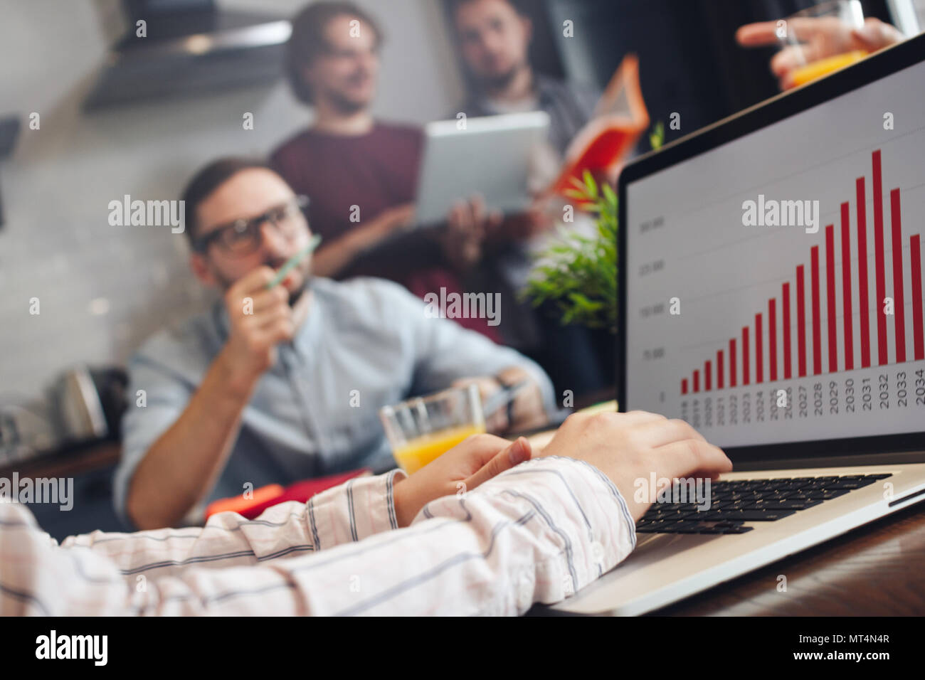 Group of young coworkers or finance analysts discuss about company indicators. Graph and diagram on laptop screen. Teamwork process concept - Stock Image