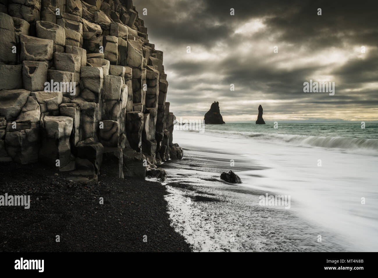 Famous Reynisfjara black beach with basalt coloumns and the Reynisdrangar sea stacks. - Stock Image