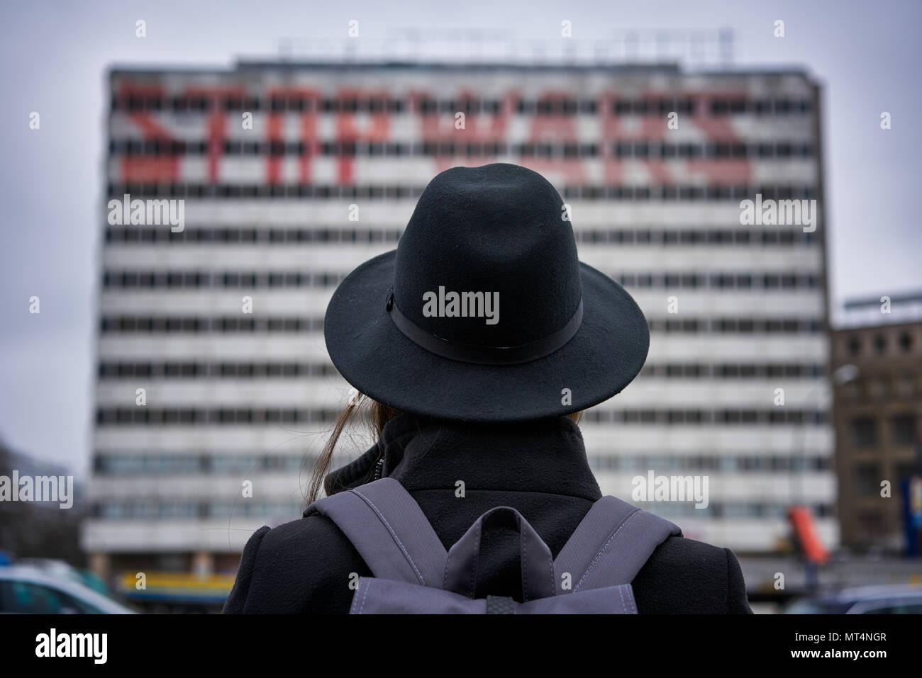 Berlin, Germany - April 4, 2017: Girl/Woman looking at 'Stop Wars' Graffiti on a building in Berlin Alexanderplatz - Stock Image