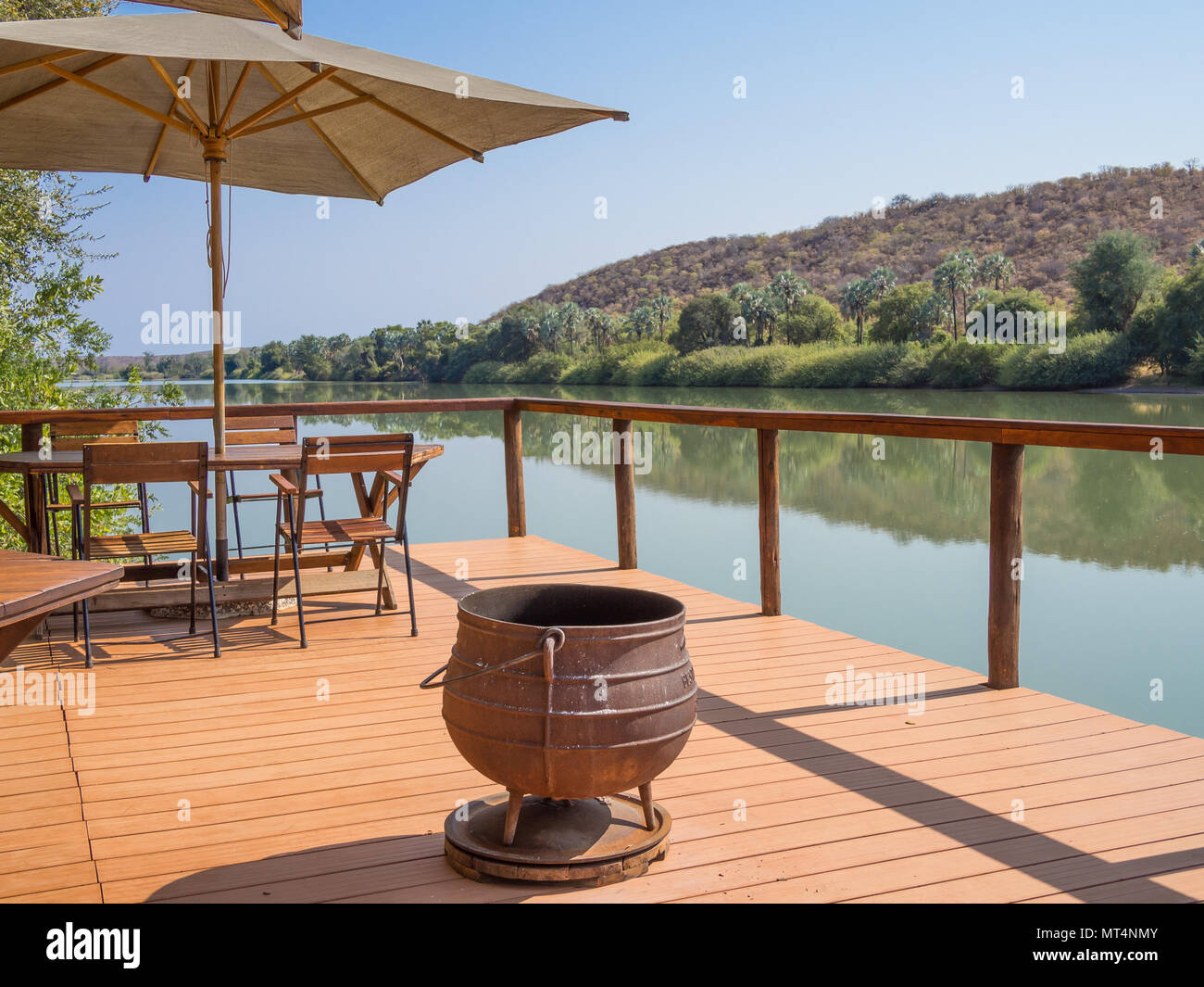 Ruacana, Namibia - July 22, 2015: Wooden terrasse with chairs, umbrealla, table and cast iron pot at Kunene River - Stock Image