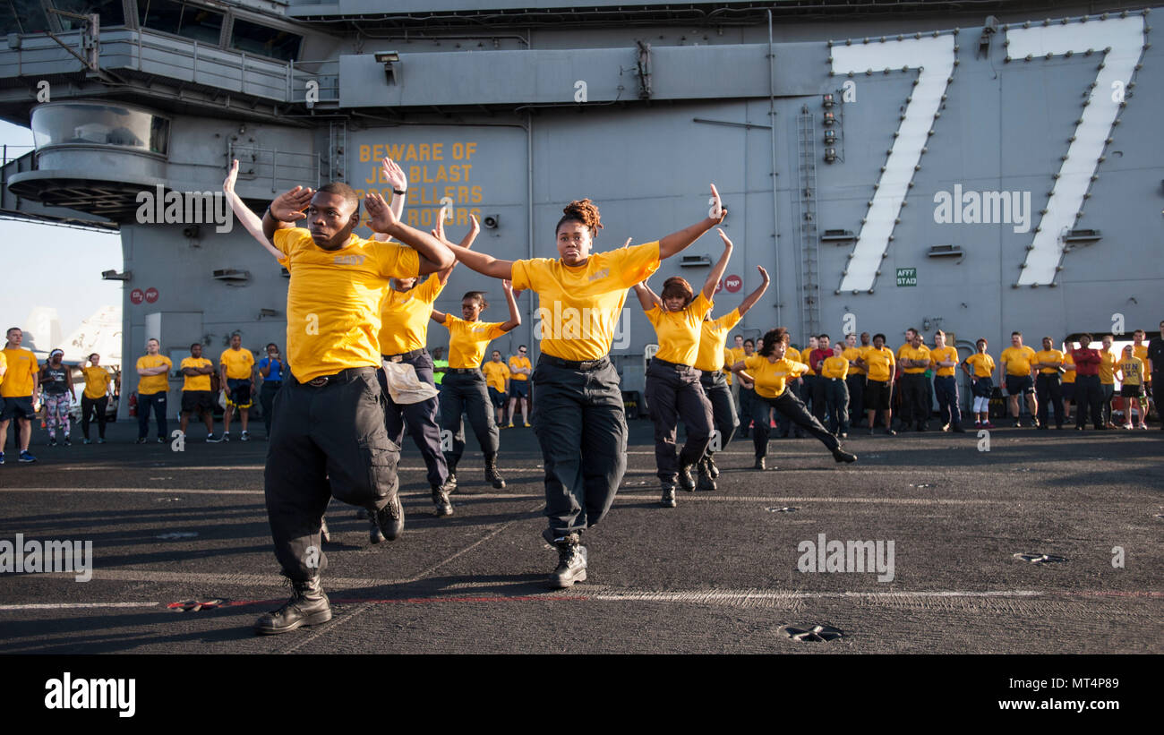 170722-N-ME396-146 MEDITERRANEAN SEA (July 22, 2017) The 77 PSI step team performs before the Suicide Prevention and Awareness Month 5K run aboard the aircraft carrier USS George H.W. Bush (CVN 77). The ship and its carrier strike group are conducting naval operations in the U.S. 6th Fleet area of operations in support of U.S. national security interests in Europe and Africa. (U.S. Navy photo by Mass Communication Specialist 3rd Class Tristan B. Lotz/Released) - Stock Image