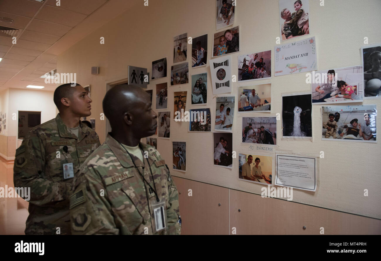 Chaplain (Capt.) John Appiah, 455th Air Expeditionary Wing, and Staff Sgt. Christopher Rodriguez, 455th AEW chaplain assistant, look at pictures of Afghan children in a hospital at Hamid Karzai International Airport, Kabul, Afghanistan, July 23, 2017. Religious support teams from Bagram Airfield visit six different locations in Afghanistan where a chaplain is not presently deployed. (U.S. Air Force photo by Staff Sgt. Benjamin Gonsier) Stock Photo