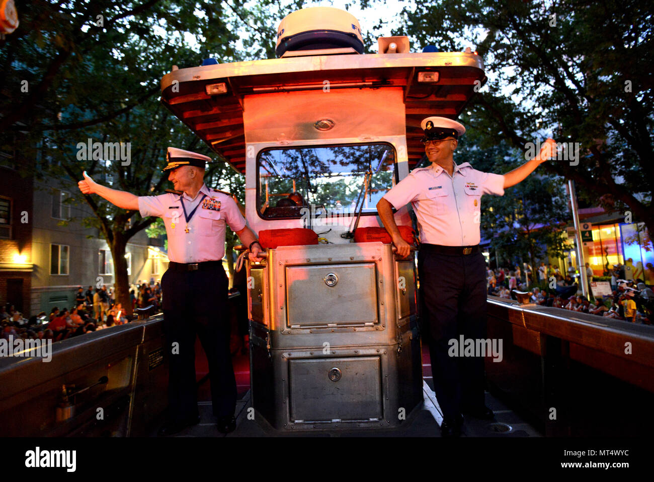 Rear Adm. David Throop, commander, U.S. Coast Guard 13th District, and Master Chief Petty Officer Sean McPhilamy, 13th Distirct Command Master Chief, wave to spectators, July 29, 2017, at the 68th Seafair Torchlight Parade. Throop and McPhilamy rode along in a 26-foot boat from the Aids to Navigation Team Puget Sound. U.S. Coast Guard photo by Petty Officer 1st Class Ayla Kelley. - Stock Image