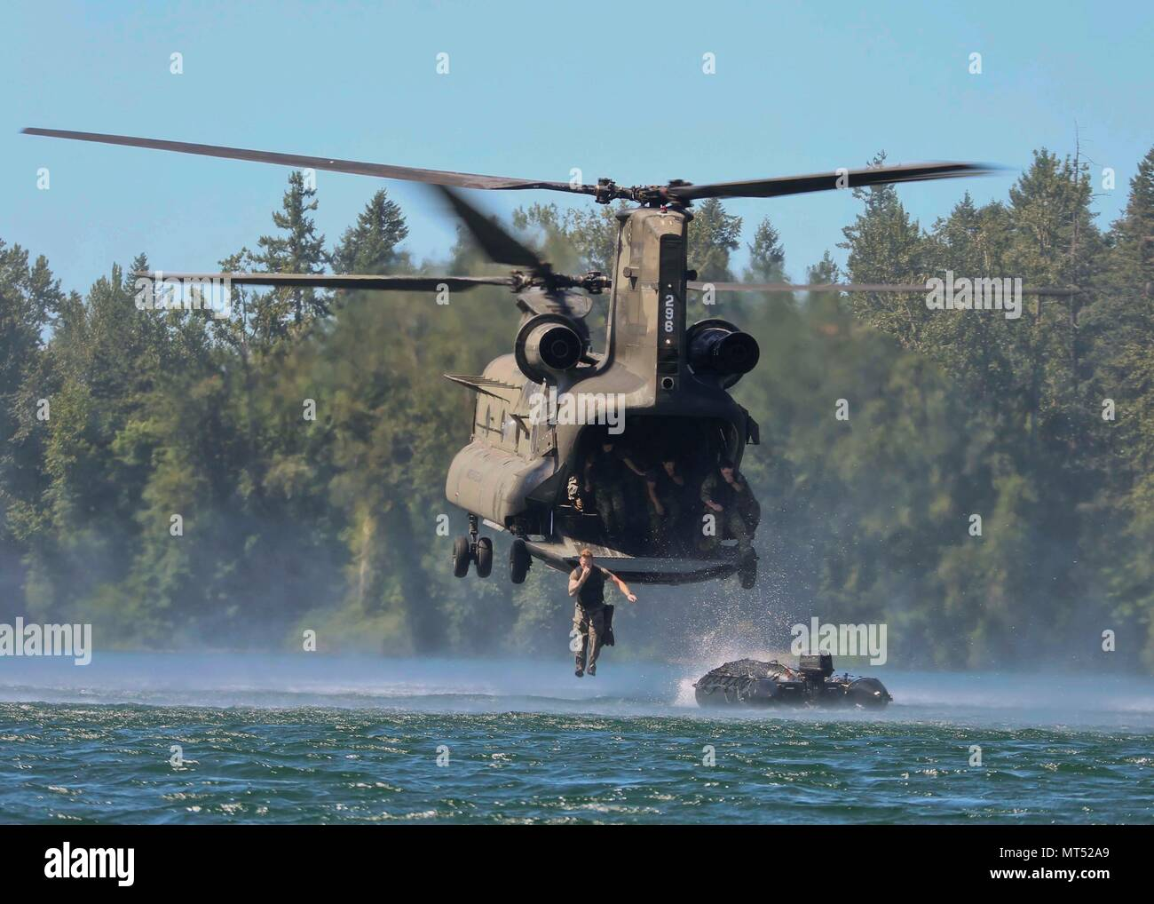 Green Berets assigned to 1st Special Forces Group (Airborne) jump into American Lake after the boat departs out the back of a CH-47 Chinook on Joint Base Lewis-McChord, Washington on July 25, 2017. This is called helocast training and prepares Soldiers to rapidly access a shoreline via helicopter insertion offshore. (U.S. Army Photo by Sgt. Codie Mendenhall/Released) - Stock Image