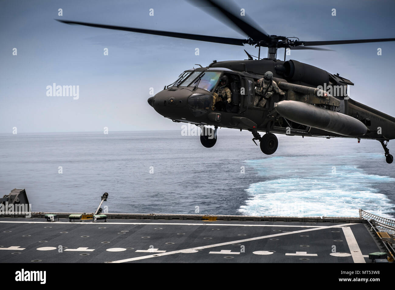 U.S. Army UH-60 Blackhawk from 1-228th Aviation Regiment Charlie Company conduct deck landing qualification aboard the USNS Spearhead off the coast of Honduras in the Caribbean Sea, July 27, 2017. The 1-228th C-Company deck landing qualification consisted of classroom instruction and 5 landings with an Instructor Pilot. Once qualified each Pilot will need to maintain their currency on a scheduled timeline. (U.S. Air National Guard photo by Master Sgt. Scott Thompson/released) Stock Photo