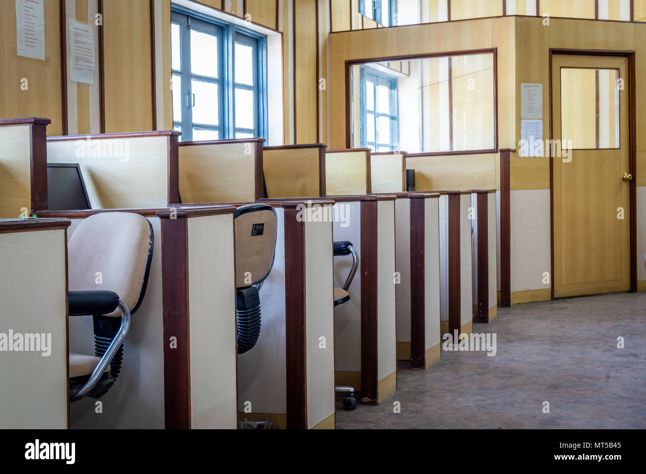 Small individual cabins with computers and chairs in an office - Stock Image