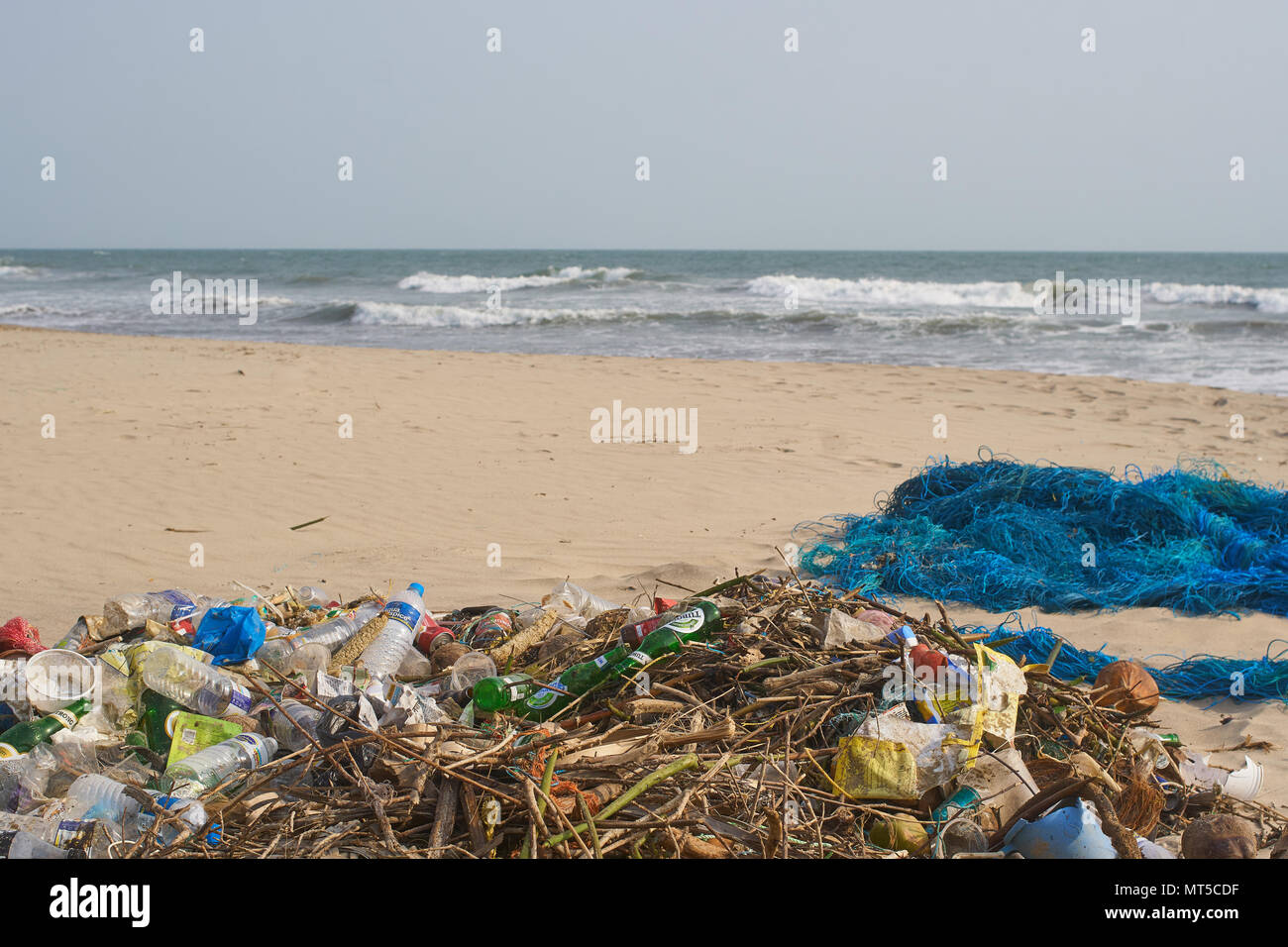 Garbage on the beach in Goa, India next to a fishing net. - Stock Image