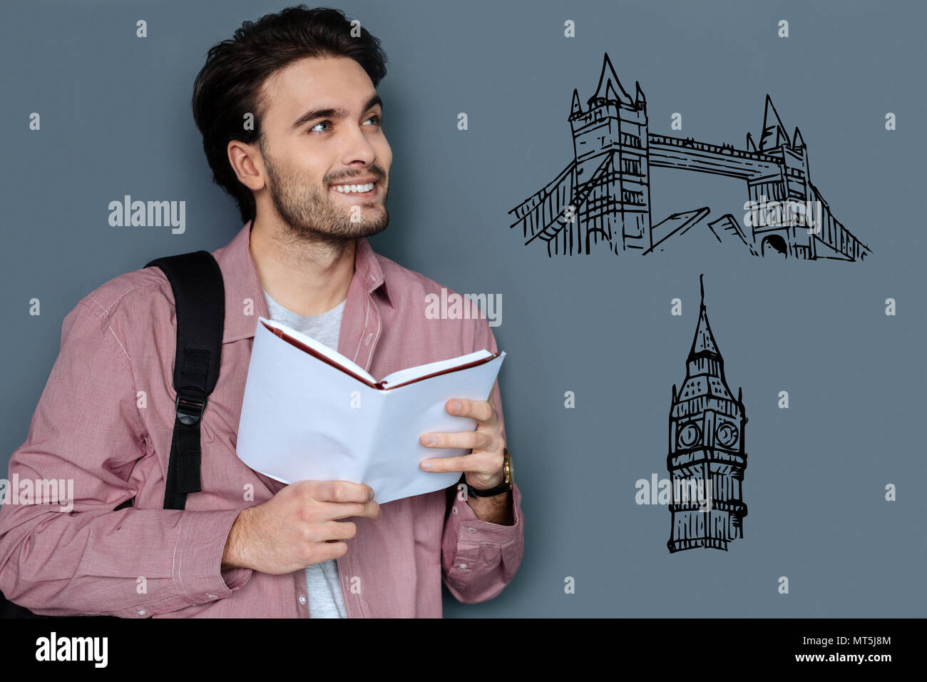 Smiling guide holding a book while talking about London - Stock Image