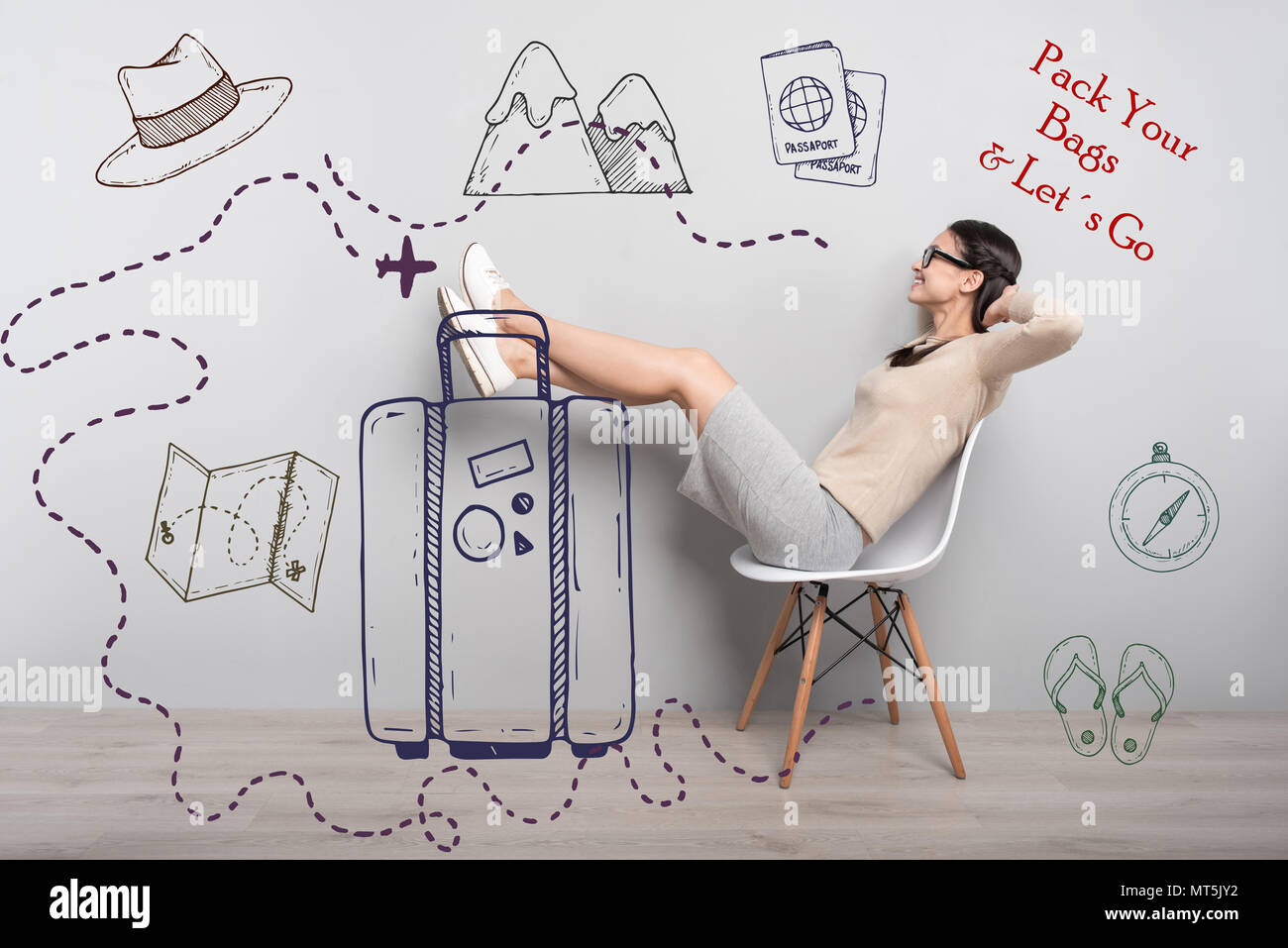 Happy student putting her feet on the suitcase and feeling good - Stock Image