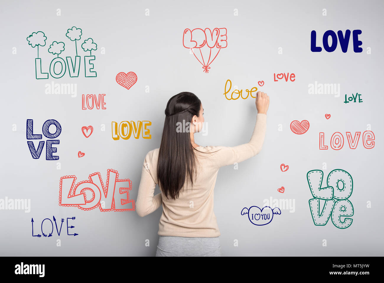 Calm young teacher dreaming about love while writing on the blackboard - Stock Image