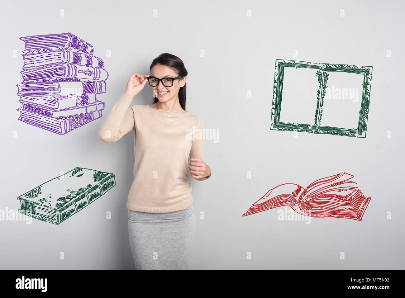 Smiling teacher touching her glasses and looking happy - Stock Image