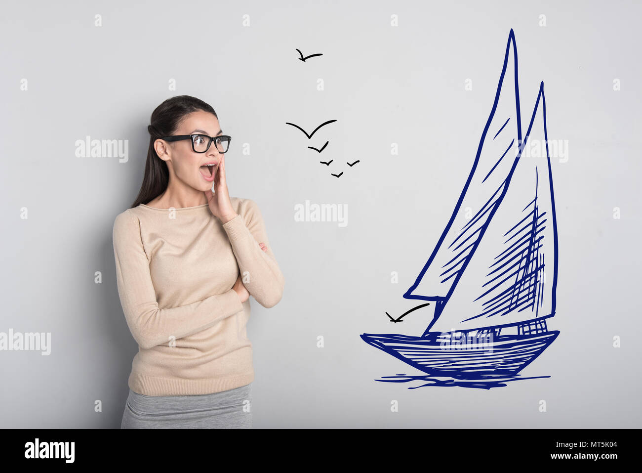 Emotional woman feeling impressed while noticing a big ship - Stock Image