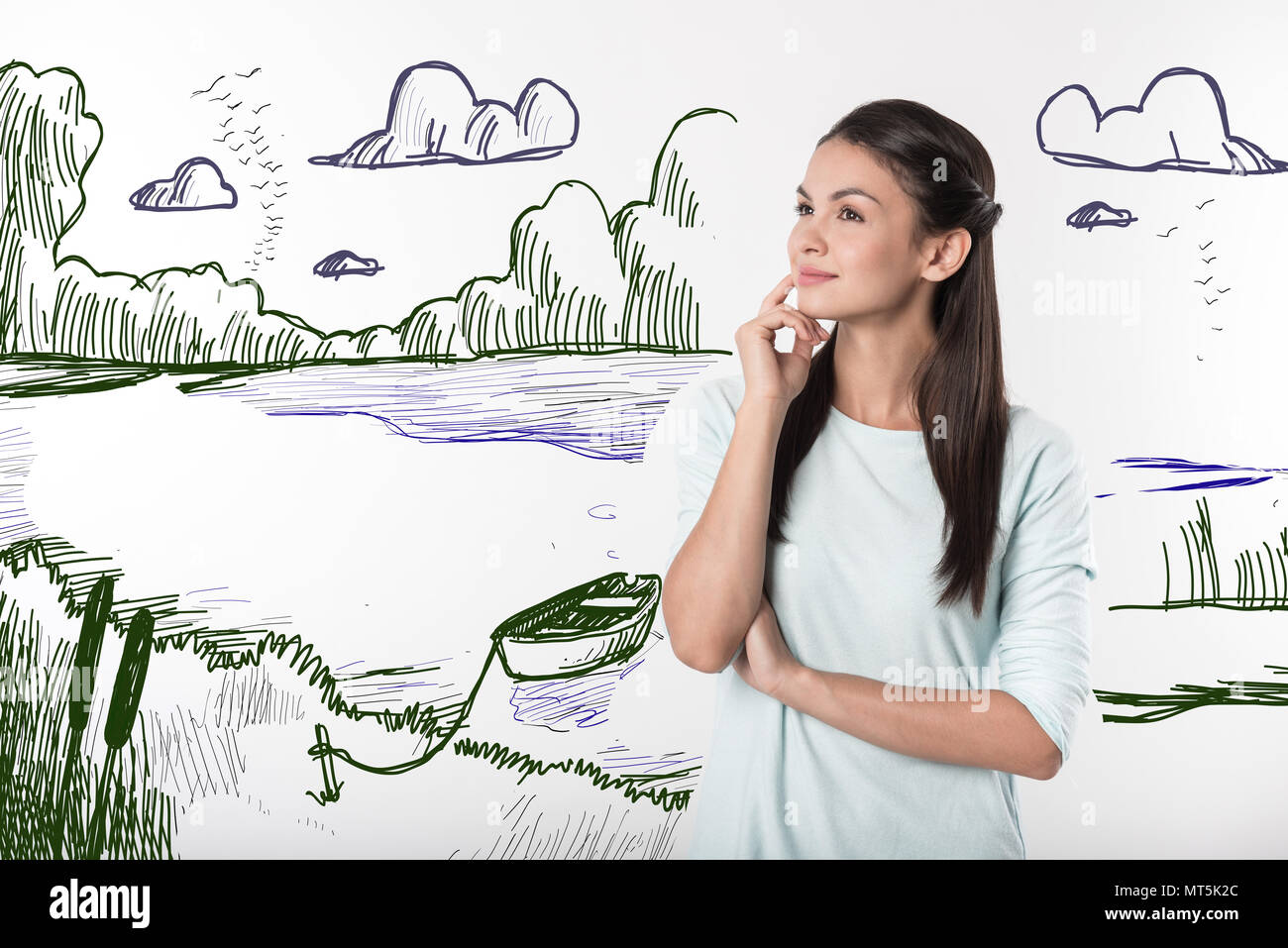 Calm secretary dreaming about pleasant holiday and smiling - Stock Image