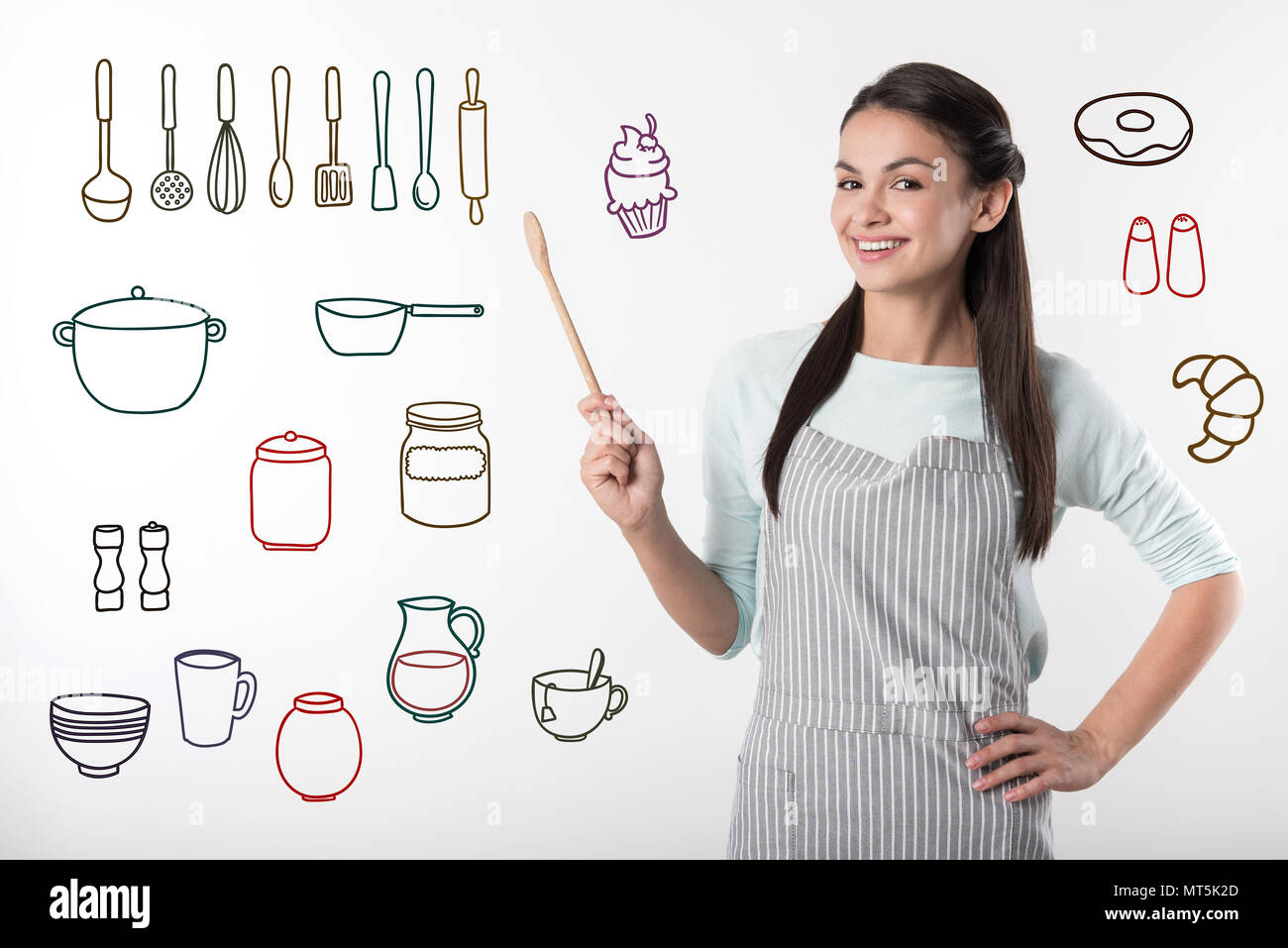 Positive professional cook smiling while being at work - Stock Image