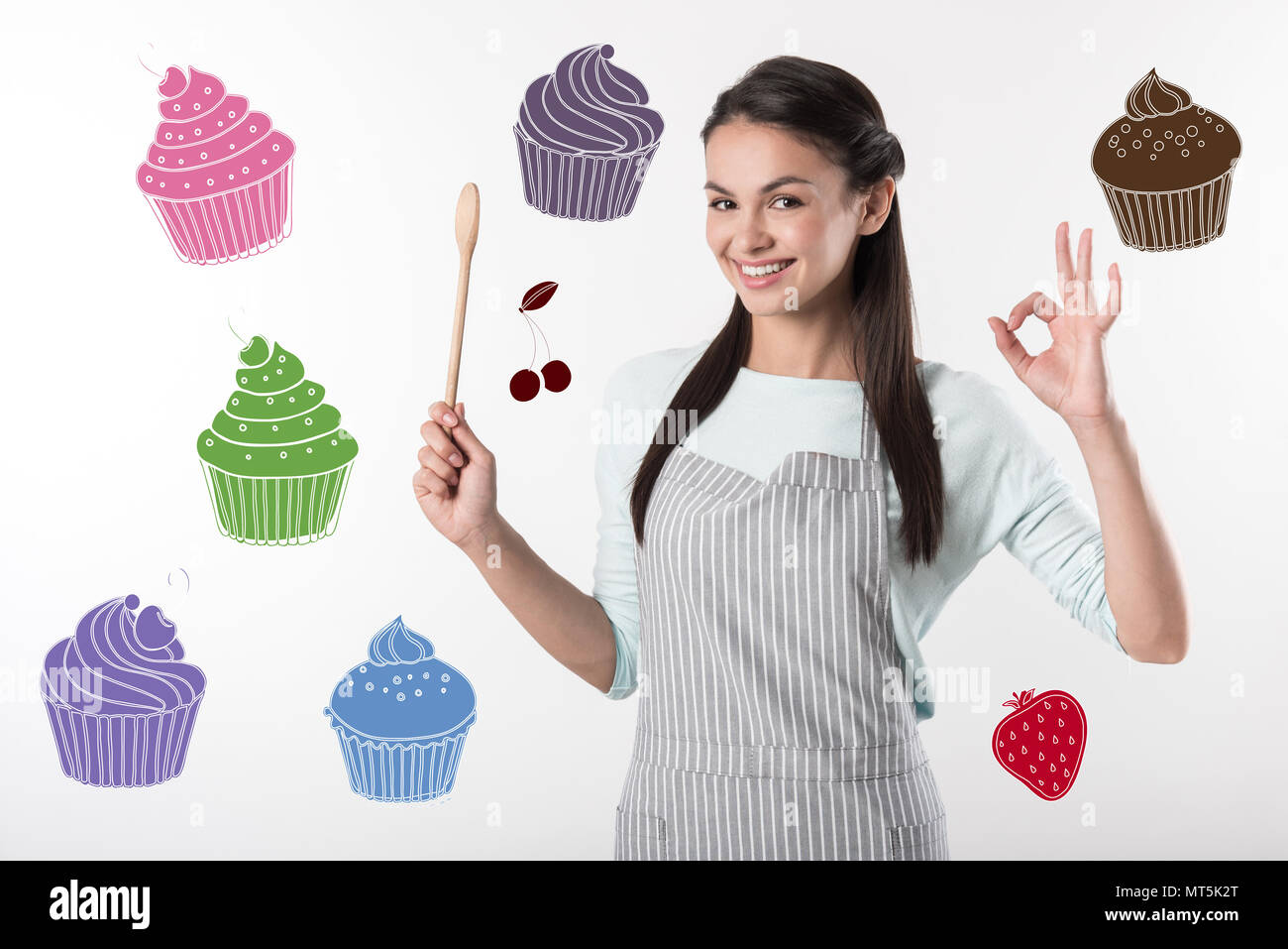 Happy cook holding a wooden spoon and looking confident - Stock Image