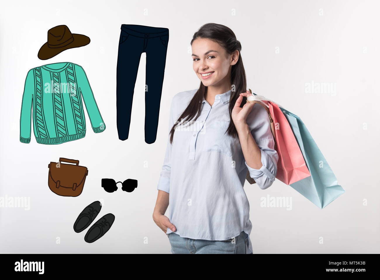 Pretty blogger smiling while choosing new clothes - Stock Image