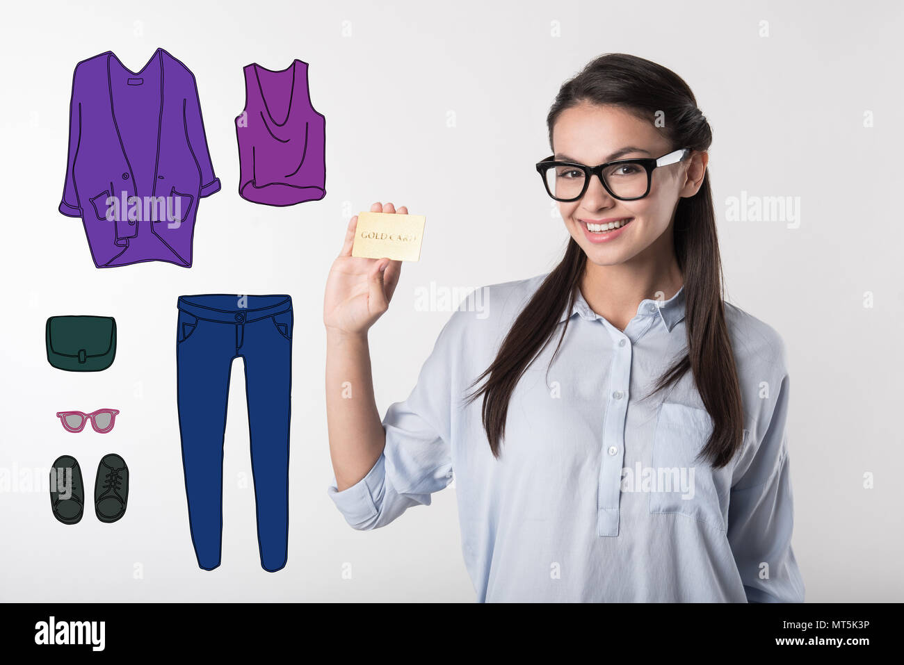 Fashionable model showing her gold card while doing shopping - Stock Image