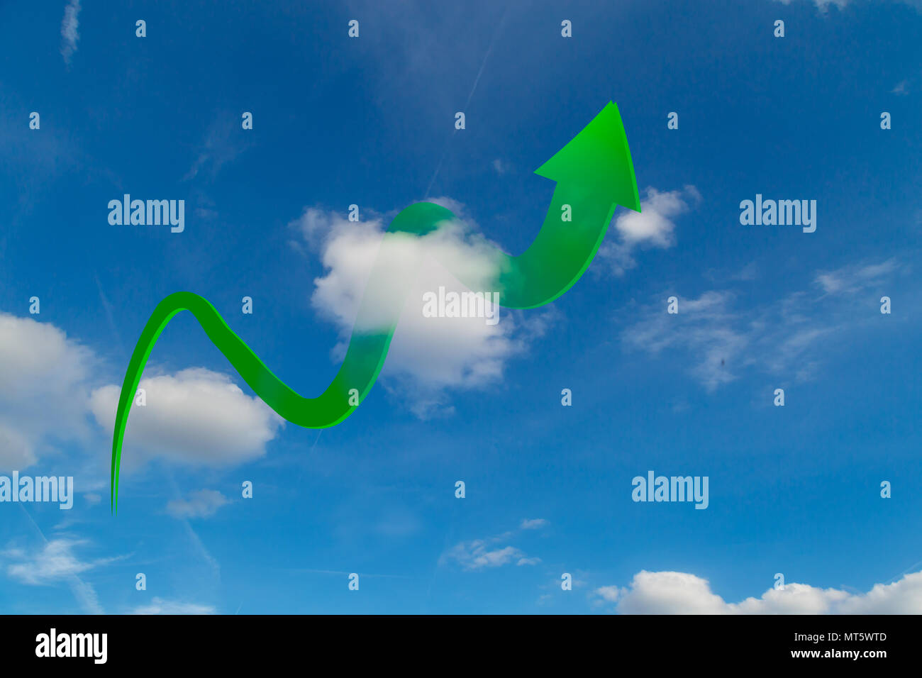 Green arrow rises in clouds on blue sky. - Stock Image