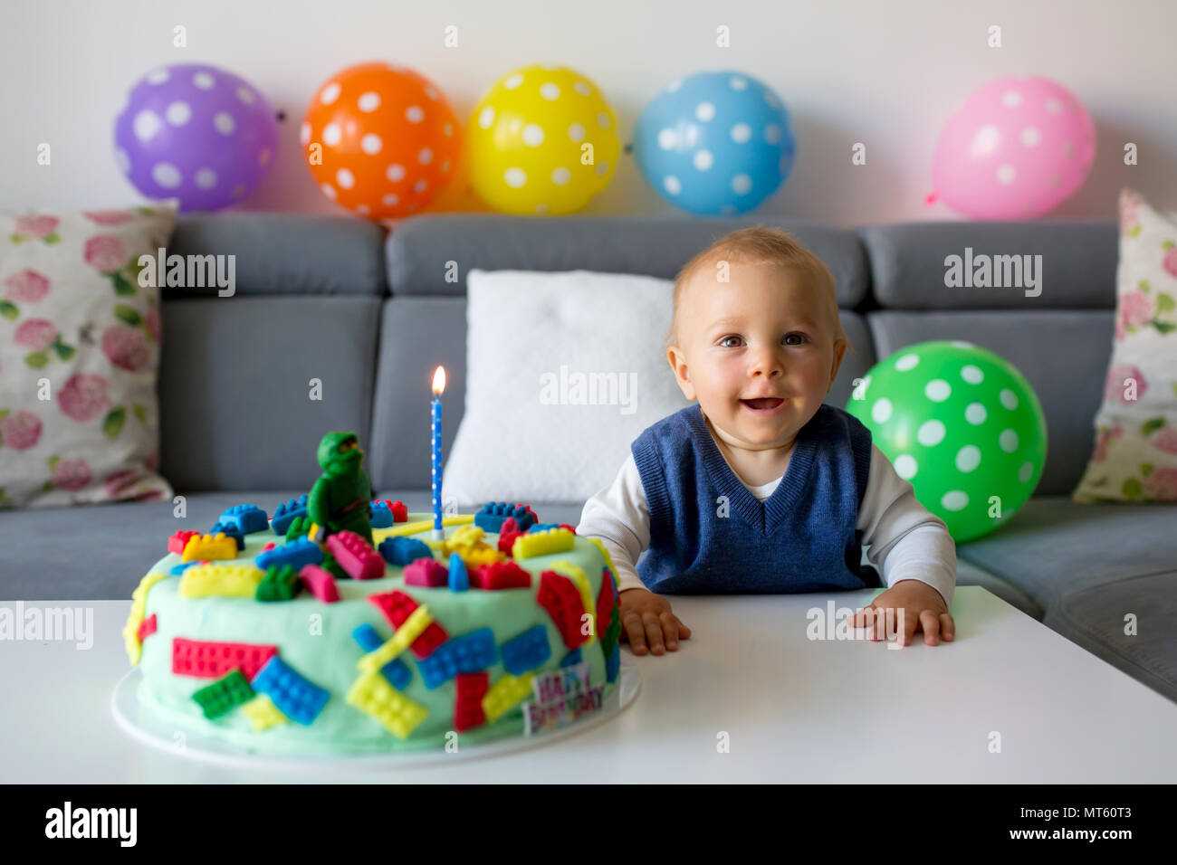 Cute Child Baby Boy Celebrating His First Birthday With Colorful Cake Candles Balloons At Home