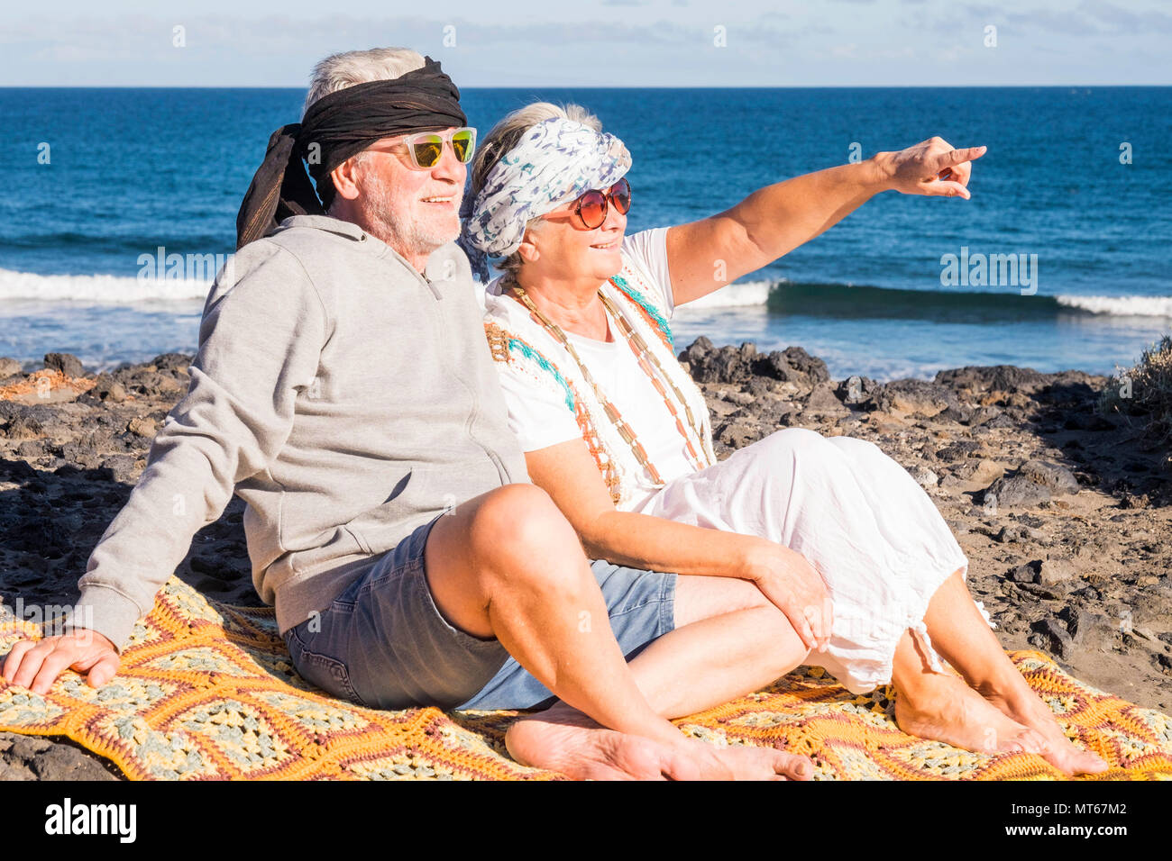 Couple of happy senior aged caucasian people sit down on the shore at the beach enjoying the summer time and the sun. Hippies alternative clothes for  Stock Photo