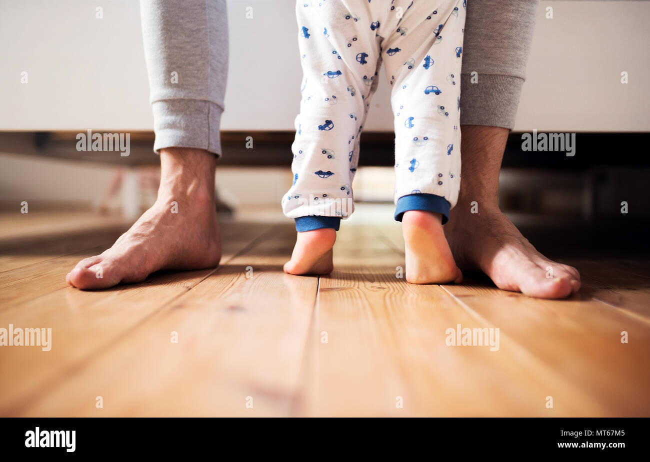 Legs of father and a toddler boy standing on the floor in bedroom at home. - Stock Image