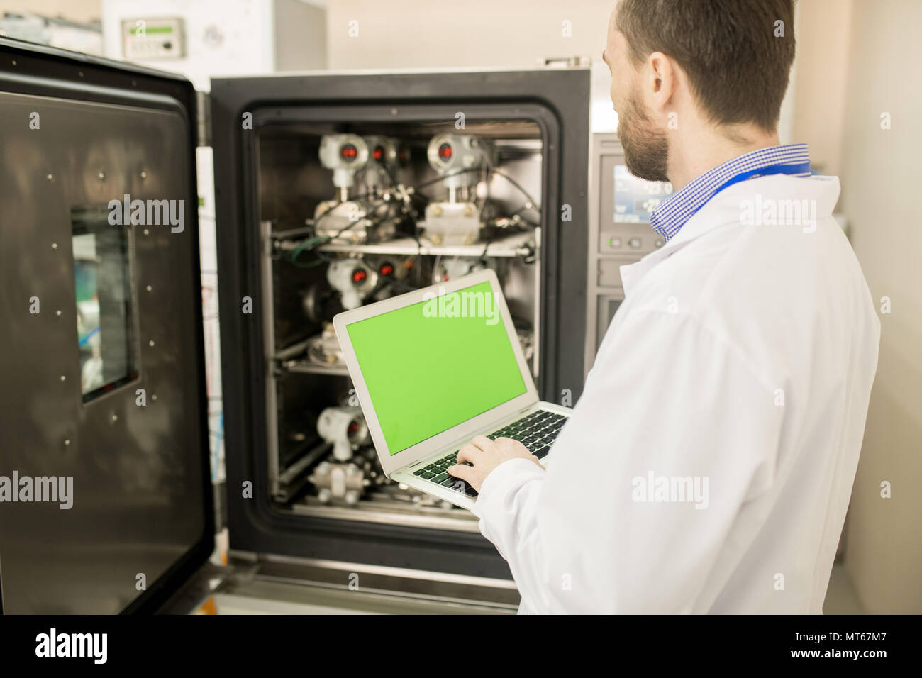 Test engineer in lab coat calibrating measuring devices - Stock Image