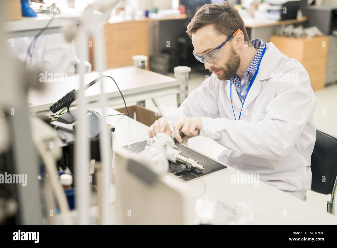 Experienced worker taking measuring device apart Stock Photo