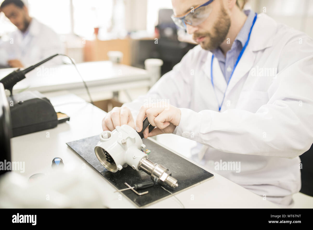 Concentrated technician finding out reason of transducer breakdo - Stock Image