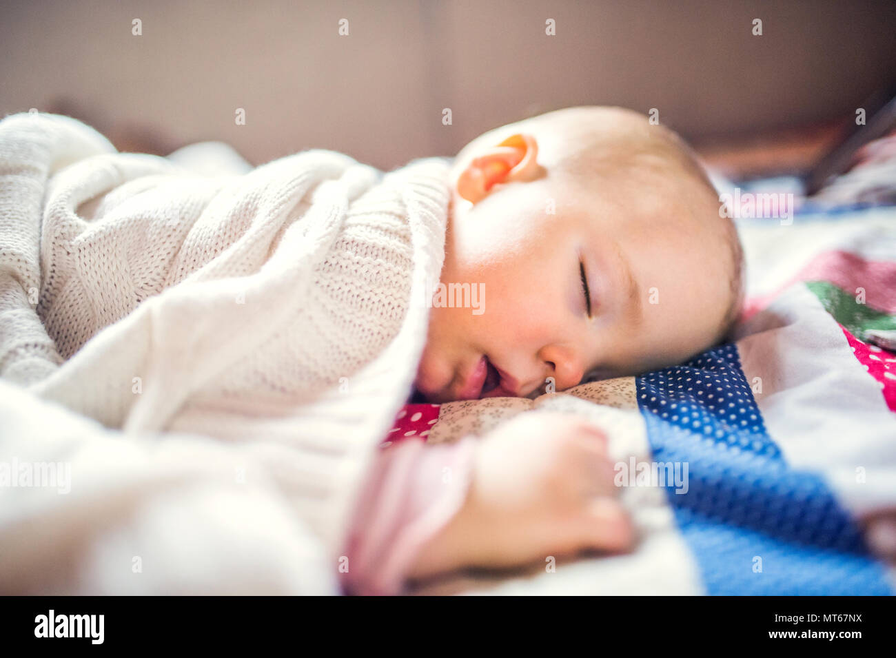 A toddler girl sleeping on a bed at home. - Stock Image