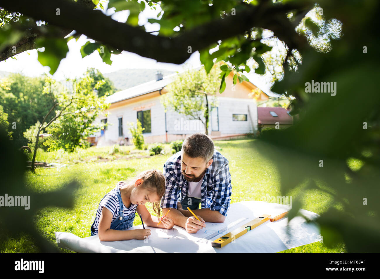 Father with a small daughter outside, planning wooden birdhouse. - Stock Image